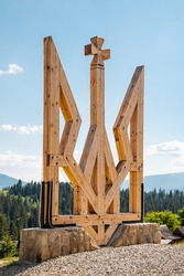 Emblem of Ukraine. A large yellow wooden trident set on a stone high in the Carpathian mountains.