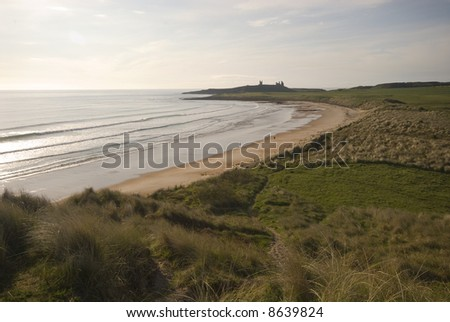 Embleton Bay and Dunstanburgh Castle overlooking the North Sea early morning