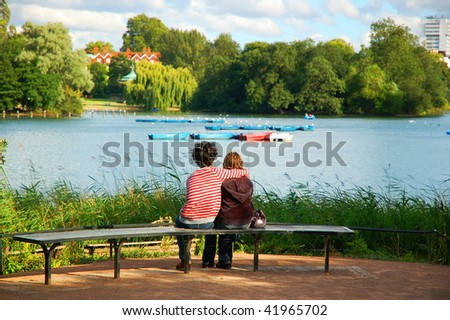 Embraced lovers on a bench at Regent's park, London. UK