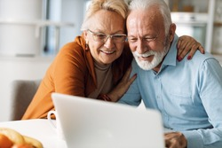 Embraced senior couple using laptop at home