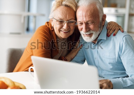 Embraced senior couple using laptop at home Foto stock ©