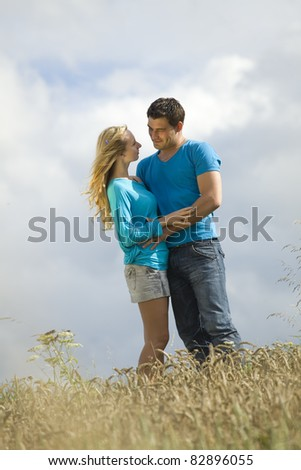 embracing couple in countryside and field