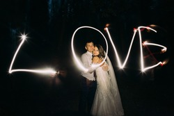 Embracing married couple and light painting of the word Love on background