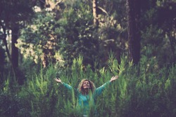 Embracing outdoor and love nature concept with happy beautiful woman in the middle of a forest trees wood in total happiness and joy - earth's day celebration to save the planet