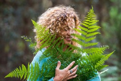 Embracing outdoors concept and love nature with portrait of beautiful young adult woman with big forest leaf and green wood in background - earth's day and care of outdoor nature