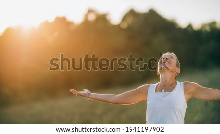 Embracing the positive energy with open arms, creating affirmative sensations, feeling energized Foto stock ©