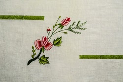 Embroidered between green ribbons, a twig with a red roses and a bud, intertwined with a coniferous twig and red berries on a white cotton fabric