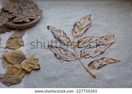 embroidered on the canvas autumn leaf with dry brown leaves and wooden Hoop