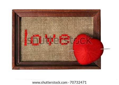 Embroidered word 'love' in the frame with knit ball in a form of a heart pierced with needle isolated on white background with clipping path