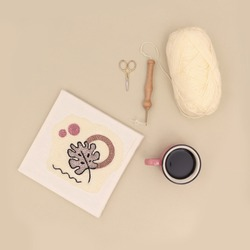 Embroidery fabric punch frame, fabric poster making of process with a wooden punch needle, wool and a coffee mug, top view minimal handicraft concept image
