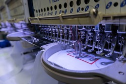Embroidery machine in progress embroidery company logo on uniform in Textile Industry at Garment Manufacturers.