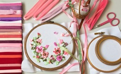 Embroidery process with satin ribbons of spring flowers and an accessories for needlework (These pictures of embroidery and embroidery with satin ribbons were performed by the author of the images)