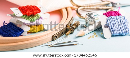 Embroidery set fot cross stitching. White fabric, embroidery hoop, colorful threads, scissors and needls. On blue background. Hobbies concept. Banner Stock fotó ©