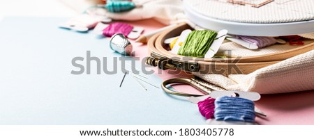 Embroidery set fot cross stitching. White fabric, embroidery hoop, colorful threads, scissors and needls. On blue background. Hobbies concept with copy space, banner. Stock fotó ©