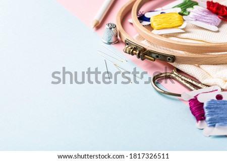 Embroidery set fot cross stitching. White fabric, embroidery hoop, colorful threads, scissors and needls. On blue background. Hobbies concept with copy space. Stock fotó ©