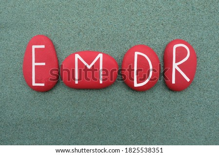 EMDR, Eye Movement Desensitization and Reprocessing, creative text composed with red colored stone letters over green sand Foto stock ©