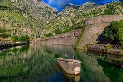 Emerald green waters of Kotor Bay or Boka Kotorska, mountains and the ancient stone city wall of Kotor old town former Venetian fortress in Montenegro