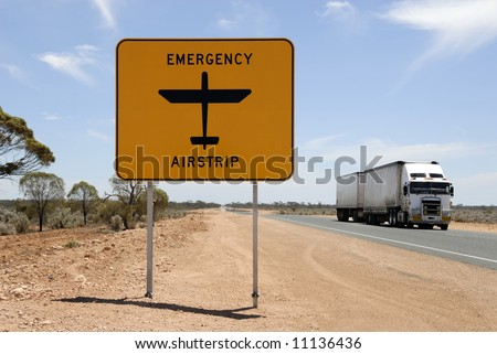 Emergency airstrip sign with road train in the Nullarbor desert in Australia