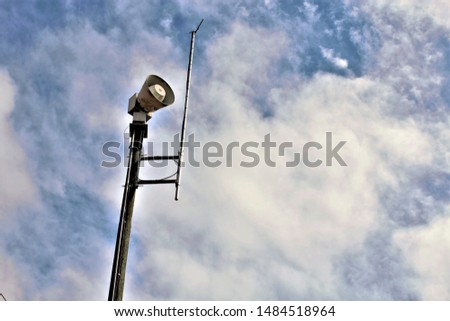 Emergency alert siren with blue sky and clouds #1484518964