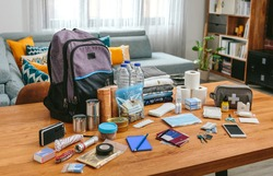 Emergency backpack equipment organized on the table in the living room