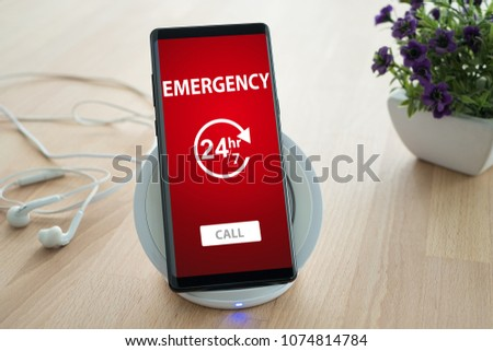 Emergency call concept. Mobile smartphone is placed on a wireless fast charger.