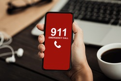 Emergency Call Concept. Top view of hands holding smart phone with number 911 on red screen over office background