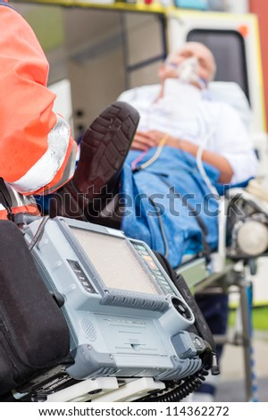 Emergency defibrillator patient with oxygen mask on ambulance stretcher