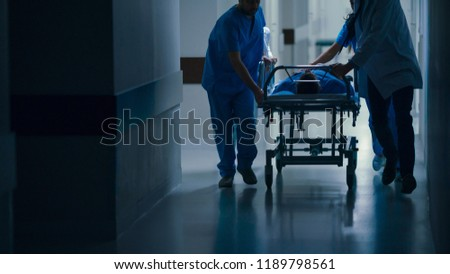 Emergency Department: Doctors, Nurses and Paramedics Push Gurney / Stretcher with Seriously Injured Patient towards the Operating Room. #1189798561