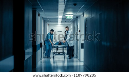 Emergency Department: Doctors, Nurses and Paramedics Run and Push Gurney / Stretcher with Seriously Injured Patient towards the Operating Room. Bright Modern Hospital with Professional Staff.