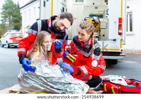 Emergency doctor and paramedic or ambulance team helping accident victim