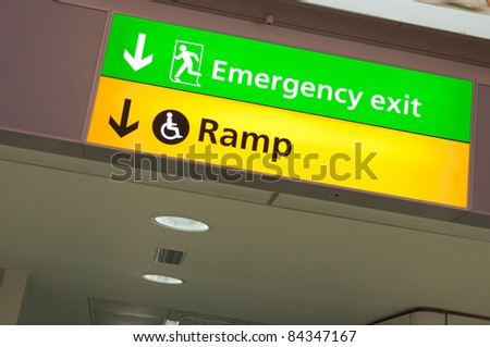 emergency exit and handicapped ramp sign at a international airport corridor