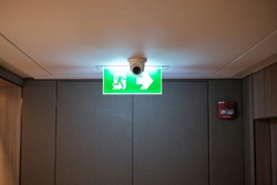 Emergency exit sign at the corridor in building. Green fire exit sign hanging on ceiling on dark corridor in building near fire emergency exit door. Green emergency exit sign.
