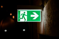 Emergency exit sign illuminated with dark background.