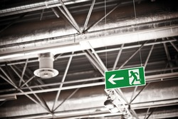 Emergency exit sign under the ceiling of a fair hall