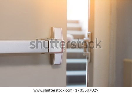 Emergency fire exit door. Closed up latch and rusty door handle of emergency exit. Push bar and rail for panic exit. Open one way door.  steel of handle for the white door fire exit