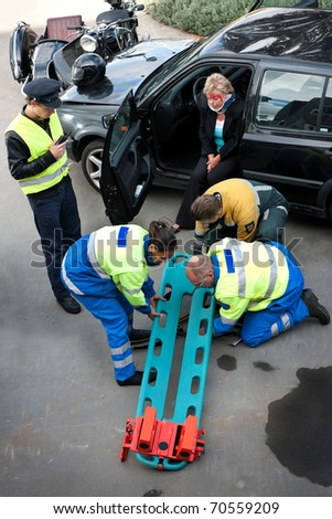 Emergency Medical Services team preparing a stretcher with head block for an injured driver