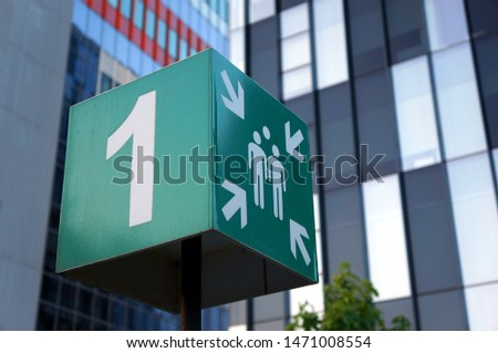 Emergency meeting point sign outside modern office buildings. ISO standardized pictogram for a fire safety assembly point. #1471008554