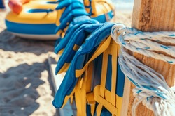 Emergency rescue equipment important for life security in the water or the sea. Many colorful yellow blue marine life vest signal jackets or life vest hanging a on the beach
