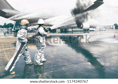 Emergency Services Training Institute fire truck fights a burning plane,fireman water injection in the airport. #1174340767