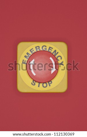 Emergency stop button on red wall
