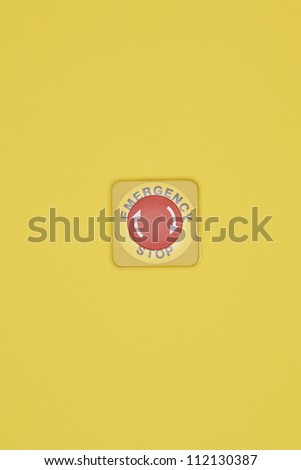 Emergency stop button on yellow wall