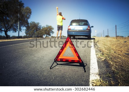 Emergency triangle on the road. Stopped car and man calling by phone in the background.