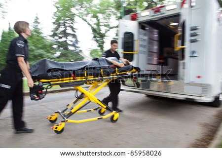 Emergency workers rushing senior woman into an ambulance
