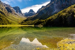 Emily peak reflecting in McKenzie lake, Routeburn track, South Island, New Zealand