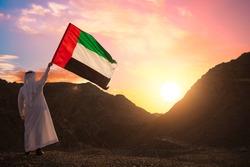Emirati Arab man holding UAE flag, celebrating the national day