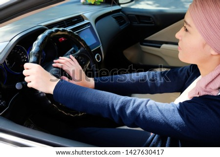 Emirati lady driver hands on car's steering wheel horn wearing head light pink turban covering her hair as muslim culture. Daylight driving #1427630417