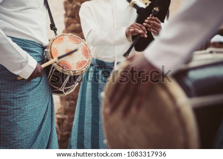 Emirati locals (GCC /Gulf) celebrating, dancing and playing traditional music and drumming in old drums in one of their culture occasion and wearing local kandura, happy with emirati yola dance.