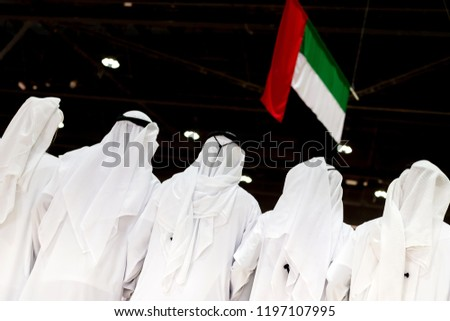 Emirati men looking at the UAE flag, concept of patriotism and celebration of the national day
