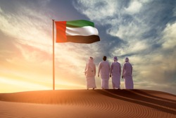Emirati Young men standing on sand dune on the desert looking in  UAE flag celebrating national day and Uae flag day