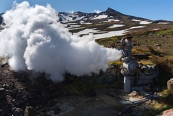 Emission of natural mineral thermal water, steam (steam-water mixture) from geological well in geothermal deposit area, geothermal power plant on slope of active Mutnovsky Volcano. Kamchatka Peninsula